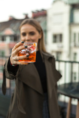 Beautiful young woman holding orange cocktail, nice ancient buildings on background