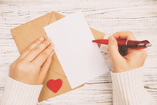 Hand of girl writing love letter on Valentine Day. Handmade postcard toned, vintage. Woman write on postcard for 14 February holiday celebration. Flat lay. Top view