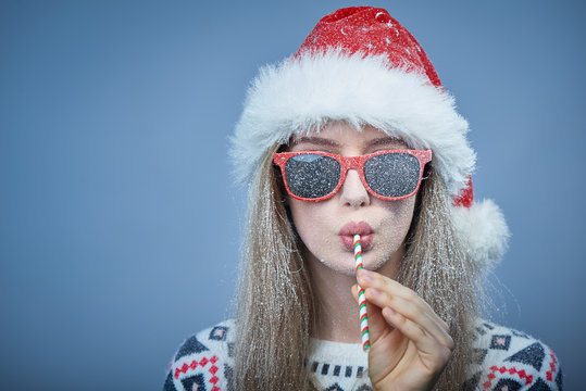 Frozen girl with snow on face wearing Santa hat and sunglasses