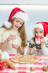mom and daughter eating a Christmas cookie with milk