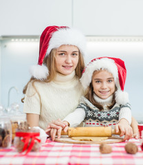 Mother and daughter in a Christmas hat prepare festive cookies at home