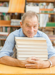 portrait of an elderly smiling man in a library with books