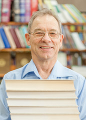 Smiling senior man holds a pile of books in the library