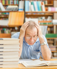 Tired elderly man reading a book in the library