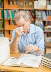 Tired senior man having a headache in library