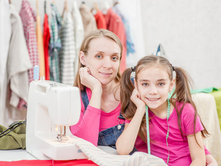 mother with her daughter in the workplace seamstresses, near the sewing machine