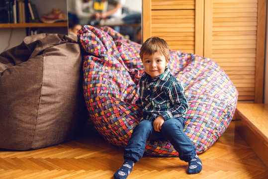 Cute little Caucasian boy sitting in bean bag and smiling. Home interior.