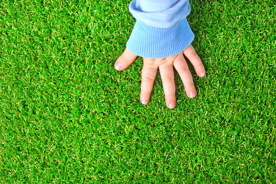 Artificial grass background. Tender hand of a baby on a green artificial turf floor.