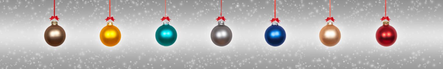 Weihnachtskugeln vor silbernen Hintergrund
