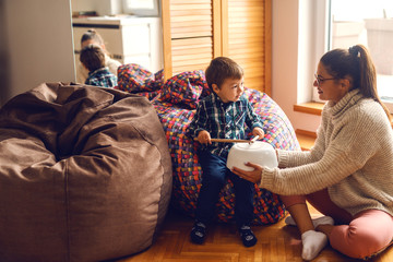 Little boy sitting in bean bag and pretending to play drums while his mother holding bowl upside down (drums). Home interior.