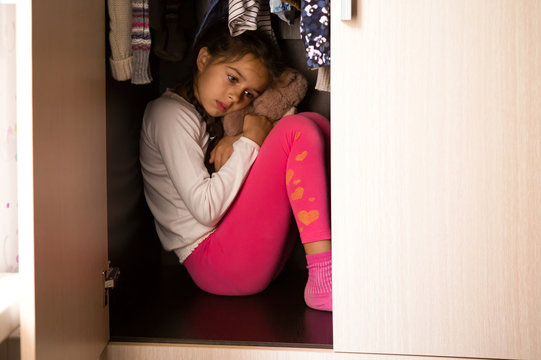 Domestic violence and abused concept. Unhappy and scared child hiding in the wardrobe and sitting there with Teddy in her hands