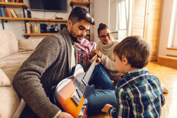 Father playing electric guitar and sitting on the floor while his family looking at him. Home interior.