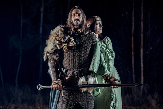 Medieval knight with his beloved lady. Dark forest on the background.