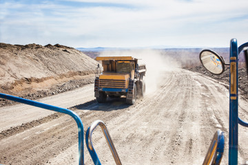 Old yellow dump truck moving in a mine. View from another truck