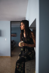 Attractive young charming lady with cup sitting in kitchen
