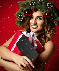 Beautiful woman with Christmas spruce fir wreath with cones and new year gift certificate present under snow flakes