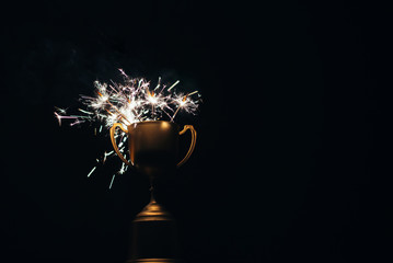 Gold trophy and Firework sparkler burning isolated black background , shining fire flame , celebration victory win success festival happy holiday concept,copy space.