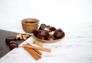 Chocolates and walnuts on a wooden background next to cinnamon and tea with bergamot