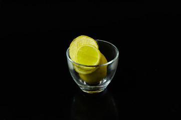lemon slice pieces arranged in tea glass closeup black background