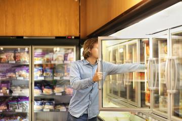 Man choosing frozen food from a supermarket freezer