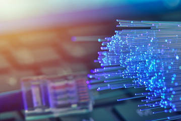 Fiber optics in blue, close up with ethernet and keyboard background, warm lens flare