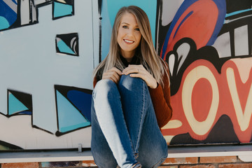 Portrait of Pretty Cute Young Blond Adult Woman Outside in Chilly Season Downtown Urban Street Art District Sitting in Front of Vibrant Colorful Graffiti Art Wall