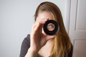 Young woman looking through camera lens and smile. Photography tools and equipment.