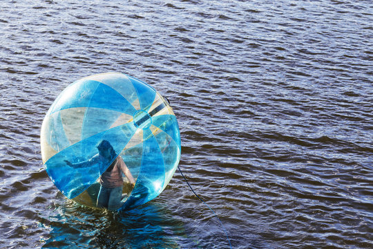Water ball (similar to zorb or Human Hamster Ball) with person inside on river surface. Vltava river in Prague