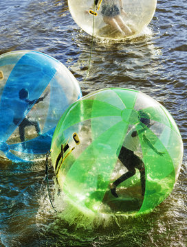 Few people in color water balls (similar to zorb or Human Hamster Ball) on river surface. Vltava river in Prague