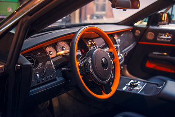Close up Luxury convertible car interior. Steering wheel, shift lever and dashboard. Driver side view. Selective focus, copy space.
