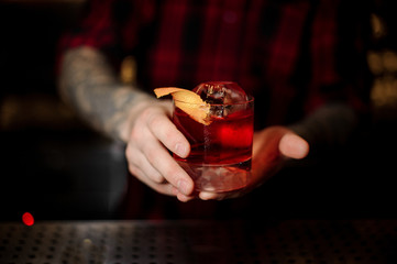 Bartender serving glass of a delicious Boulevardier cocktail with orange zest on the bar counter