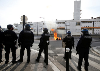 French policemen stand next to a burning trash container as youth and students protest against reform plan in the streets of Bordeaux
