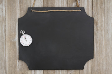 Hanging chalkboard with a stopwatch on weathered wood wall