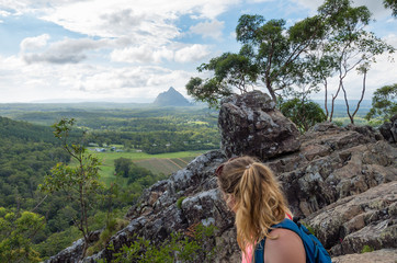 Young woman climbing down a mountain with a single peak in the background over Australian landscape