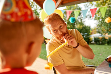 Playful father with son on a garden birthday party