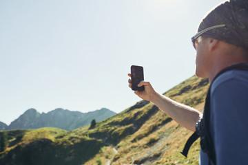 Wanderer macht Selfie vor Bergkulisse