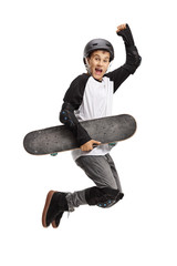 Young skater holding a skateboard and jumping
