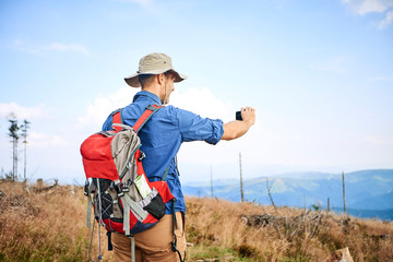 Man taking picture with his cell phone during hiking trip