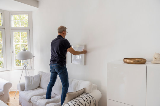 Back view of mature man hanging up picture frame at home