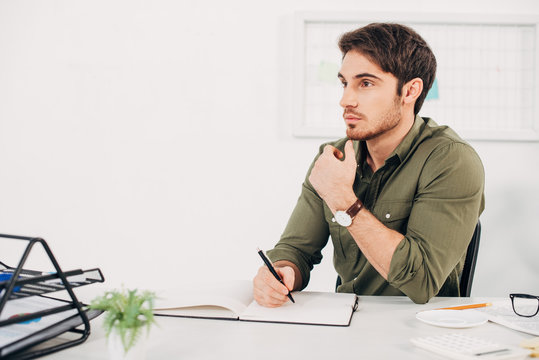 Businessman sitting at desk and thinking with pen in hand
