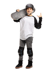 Young boy posing with a skateboard and gesturing rock and roll