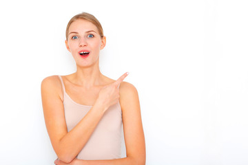 Portrait of happy surprised young woman model indicates with fore finger shows place for your advertisement or promotional text.