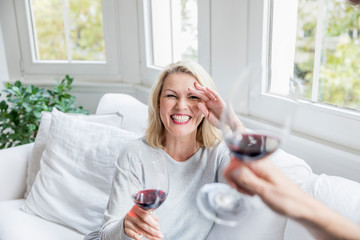 Portrait of laughing blond mature woman toasting with red wine at home
