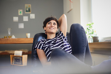Smiling woman sitting at home relaxing