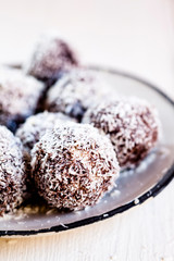 Lamington bliss balls with cashews, filled with raspberries, dark chocolate and coconut flakes