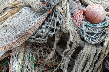 Old fishing nets with red float lay in port. Close-up