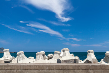 Breakwater structure with concrete blocks under cloudy sky