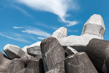 Breakwater blocks made of concrete are under cloudy sky