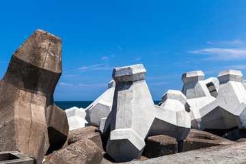 Rough concrete breakwater blocks are under cloudy sky