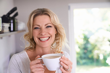 Portrait of smiling woman drinking coffee in kitchen